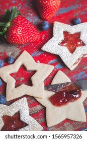 Spreading strawberry jam on star shaped sandwich sugar Christmas cookies on a rustic vintage wooden background