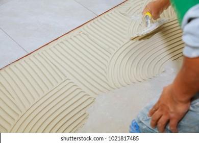 Spreading wet mortar before applying tiles on bathroom floor. puts adhesive
