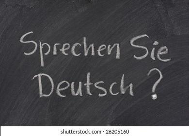 Sprechen Sie Deutsch? Do you speak German question handwritten with white chalk on a blackboard with eraser smudges