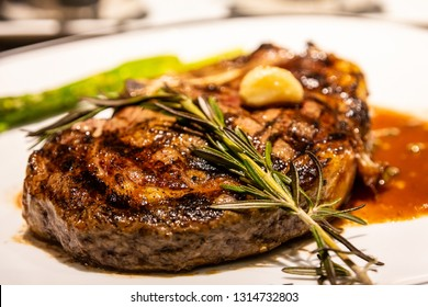 A sprig of rosemary on a fresh roasted bone-in ribeye steak with garlic, gravy and asparagus