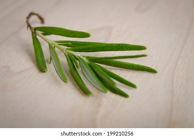 a sprig of rosemary on a wooden table
