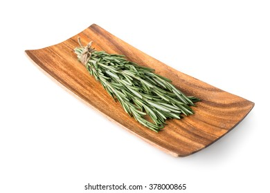sprigs of rosemary on a wooden plate isolated on white background