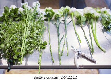 Sprigs of white flowers lie on a gray table prepared for a floral wedding bouquet. Concept of florist masterclass and wedding decor