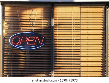 A Spring 2019 photo of an Open sign in a restaurant window on Rideau St. Ottawa, ON, CAN. The drawn blinds in the evening sunset light added vibrant color to the photo.