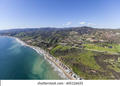 Spring aerial view of Malibu beach homes and hillsides in Southern California.