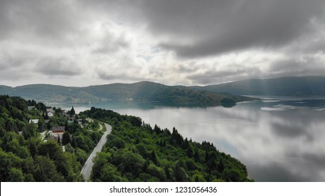 Spring aerial view over the north side of Mavrovo Lake,a mountain heaven in Mavrovo national park, Rep.of Macedonia. Dramatic scenery of the clouds are making the magic sight into the lake reflection