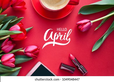 Spring background with beautiful colorful tulips, mobile phone with Hello April inscription, coffee and red lipstick on yellow table. Flat lay, top view.