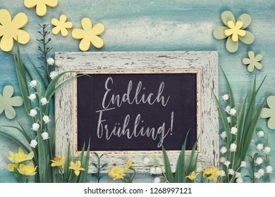 """Spring background: blackboard framed with spring flowers on green textured background. Chalk text on the board """"Endlich fruhling"""" means """"Finally Spring"""" in German. - Shutterstock ID 1268997121"""
