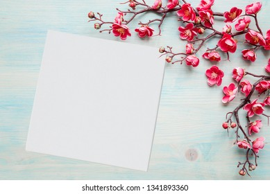 Spring background of painted blue board with branch of flowering cherry branch covered with pink flowers as a border, with white square blank paper sheet or canvas as place for text