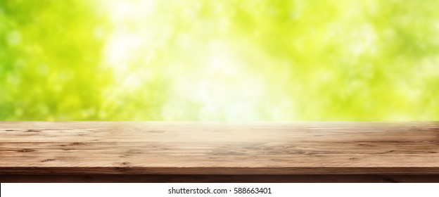 Spring background with sun in front of an empty wooden table for a concept