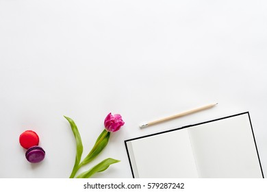 Spring background with tulips and macaroons, top view