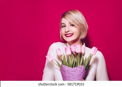 Spring Beautiful cheerful girl smiling and holding a bouquet of tulip flowers. Young happy woman. Surprise at the 8 march International Women's Day.