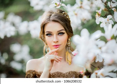 Spring Beautiful romantic girl in fashion  lace dress standing in blooming garden. Dreaming young model between magnolia trees.