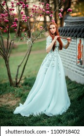 Spring Beautiful romantic red haired girl in lace dress standing in blooming garden. Dreaming young model looking at camera with flute.