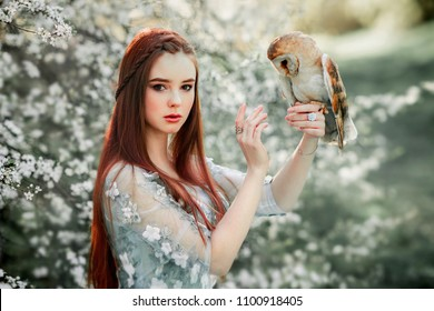 Spring Beautiful romantic red haired girl in blue lace dress standing in blooming garden with owl. Dreaming young model looking at camera. Fantasy art work.