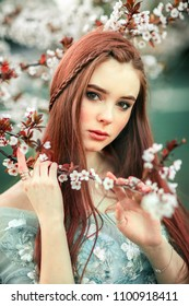Spring Beautiful romantic red haired girl in lace dress standing in blooming garden. Dreaming young model looking at camera.