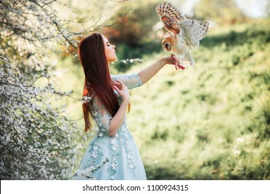 Spring Beautiful romantic red haired girl in  lace dress standing in blooming garden. Dreaming young model with owl