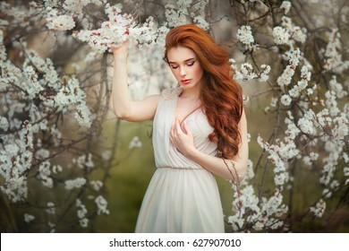 Spring Beautiful romantic red haired girl standing in blooming garden. Tenderness Young model looking down