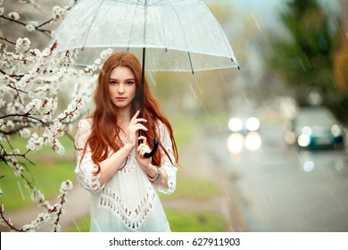 Spring Beautiful romantic red haired girl in white lace dress and jeans standing near blooming tree with transparent umbrella.Young model near road under rain looking at camera.