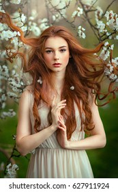 Spring Beautiful romantic red haired girl standing in blooming garden. Young model looking at camera expressive.
