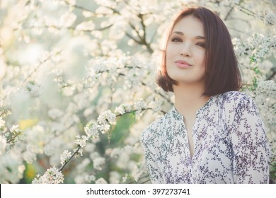 Spring beauty girl with long red blowing hair outdoors. Blooming sakura tree. Romantic young woman portrait