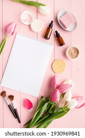 Spring and beauty. Top view of cosmetics and pink and white tulips with calendar or notepad for mock up flat lay on pink wooden background