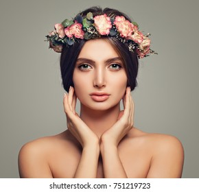 Spring Beauty. Young Woman with Healthy Skin and Roses Flowers. Beautiful Model Girl on Background