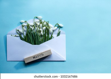 Spring beginning concept.  Envelope with snowdrops, wooden inscription - March on light blue background.