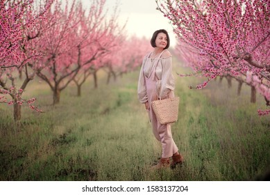 in spring, in a blooming peach garden, a woman in a pink jumpsuit with a wicker basket is posing