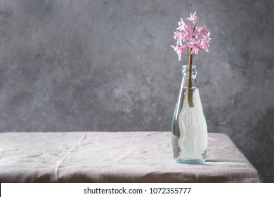 Spring blooming pink hyacinth in blue glass bottle standing on table with linen tablecloth.