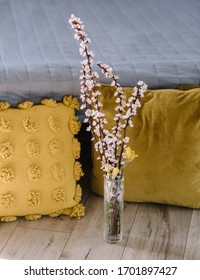 spring blossom bouquet on wooden floor in bedroom near pillows, with sun rays from window