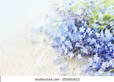 Spring blue forget-me-nots flowers posy on wooden background , pastel background, selective focus, toned floral card