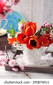 Spring bouquet in colorful mugs on color wooden background