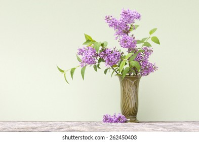 A spring bouquet of fresh cut fragrant purple lilacs in a vase with focus on lilacs, plenty of space for text
