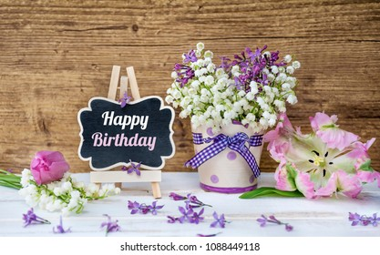 Spring Bouquet of Lilly of the Valley and Lilac  and Happy Birthday Message on a Wooden Background