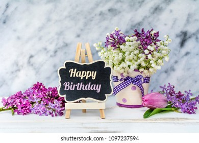 Spring Bouquet of Lilly of the Valley and Lilac  and Happy Birthday Message on a Marble Background