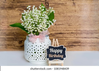 Spring Bouquet of Lilly of the Valley with Pink Ribbon and Happy Birthday Message on a Wooden Background