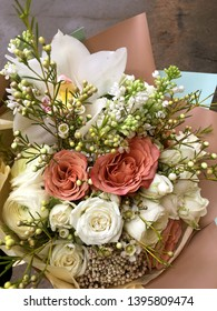 Spring bouquet of mixed colorful flowers. Flowers bouquet including white orchid Cymbidium , white Eustoma, white spray rose, white hamelacum. Beautiful bright flowers background. Beige bouquet