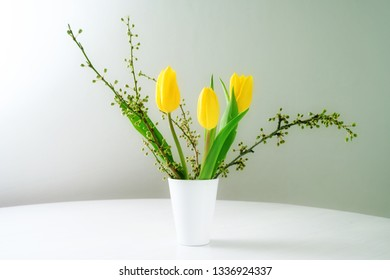 spring bouquet, vase with yellow tulips and branches on a white table against a blue gray background with copy space, selected focus, narrow depth of field