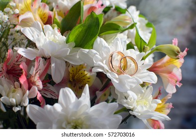 spring bouquet with white flowers and wedding rings