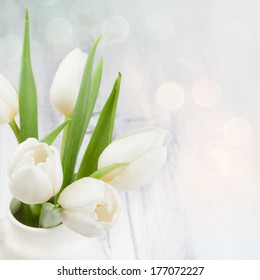 Spring bouquet of white tulips with green leaves over white old background, selective focus