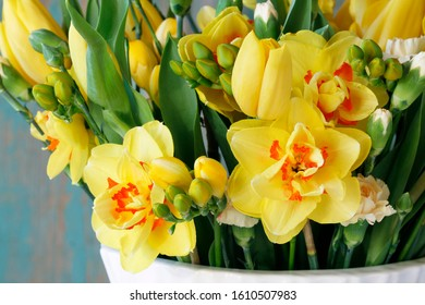 Spring bouquet with yellow tulips, carnations and daffodils. Fresh flowers in a white vase.