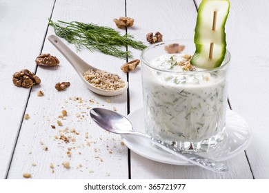 Spring bulgarian cold soup tarator with yogurt, cucumber, garlic, dill, walnuts in glass beakers on a white wooden table. Selective focus