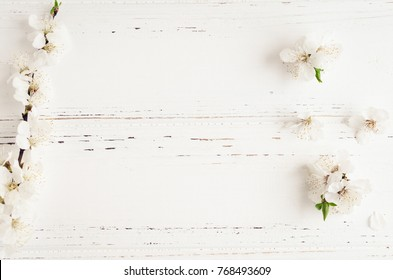 Spring cherry blossom on white rustic wooden table. Springtime flowers on vintage shabby chic background with place for text. Mothers Day concept. Mother's gift. Top view. Copy space.