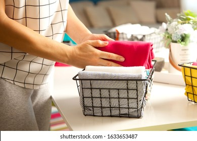 Spring cleaning of closet. Vertical tidying up storage. Neatly folded bright color clothes in the metal black baskets for wardrobe.