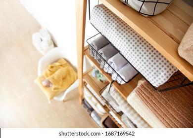 Frühlingsreinigung des Schränken. Vertikales Aufräumen des Speichers. Fein gefaltete Bettwäsche in den schwarzen Metallkörben für Kleiderschrank. Nordischer Stil.