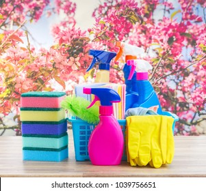 Spring cleaning concept - colorful sprays bottles and rubbers on wooden table over spring background