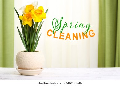 Spring cleaning concept. Daffodils in pot on wooden table against window background