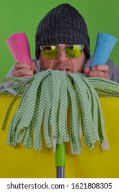 Spring cleaning concept,a funny image of a mop with a mans head on top of it the man has two clothes in his hands,he also has sunglasses and a hat on,there is a bright green background.