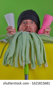 Spring cleaning concept,a funny cleaning image of a man, with his head on top of a mop head ,he is holding two cloths in his hand,there is a bright green background and a bright yellow surface.